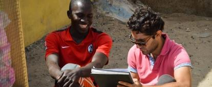 A Senegalese beneficiary discusses his business with a student doing a Micro-finance internship abroad.